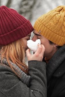 雪とカップルから作られたハート形