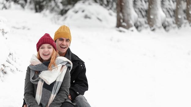 雪の中で楽しんで若い美しいカップル