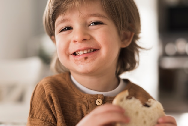 Крупным планом счастливый ребенок ест бутерброд