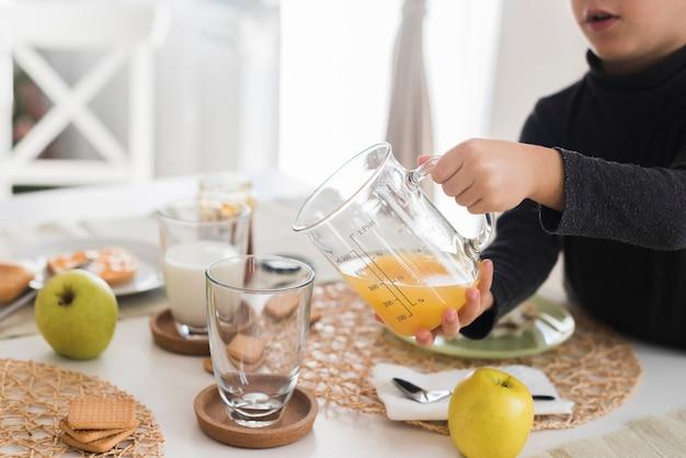 Малыш наливая апельсиновый сок в стакан
