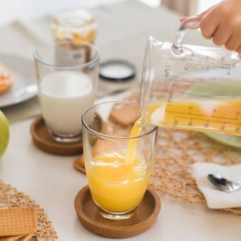 ガラスにオレンジジュースを注ぐ高角度の子供