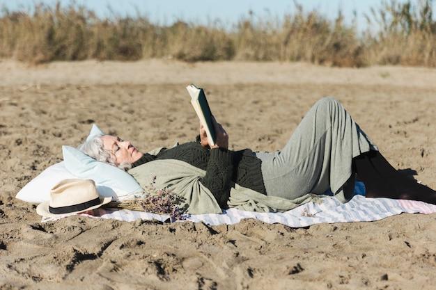 年配の女性は屋外で本を読んで