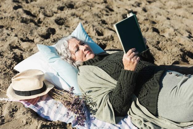 Симпатичная женщина читает книгу на открытом воздухе