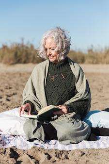 Старший леди, чтение книги вид спереди
