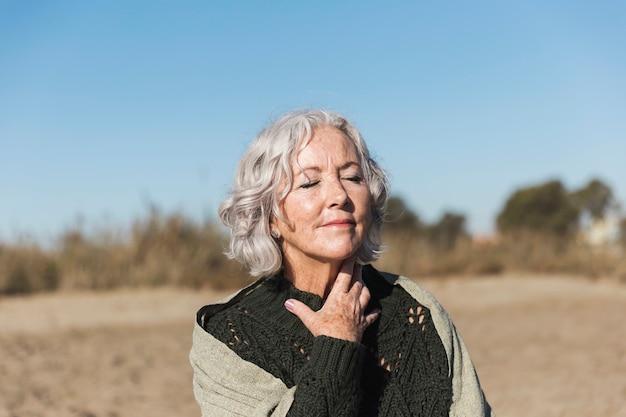 Симпатичная старшая женщина представляя средний снимок