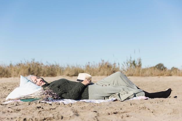Старшая женщина кладя на песок