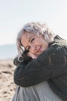 Красивая пожилая женщина позирует на улице