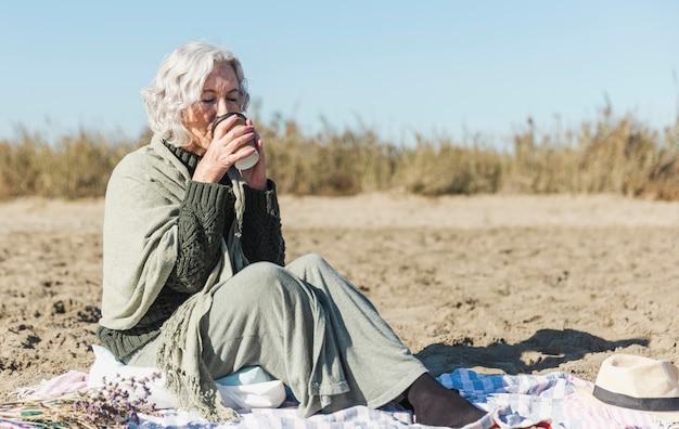 Пожилая женщина пьет кофе на открытом воздухе