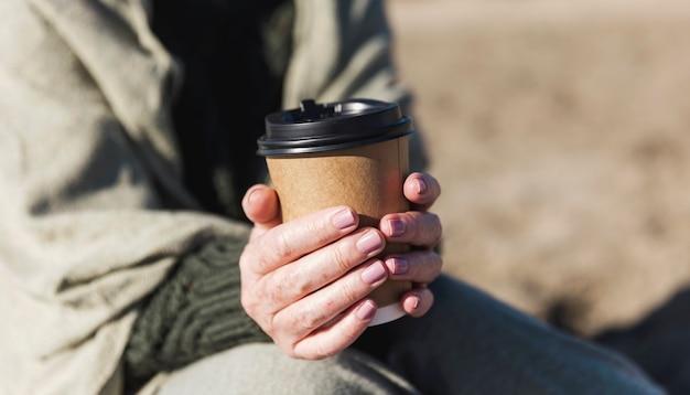 一杯のコーヒーを保持しているクローズアップの女性