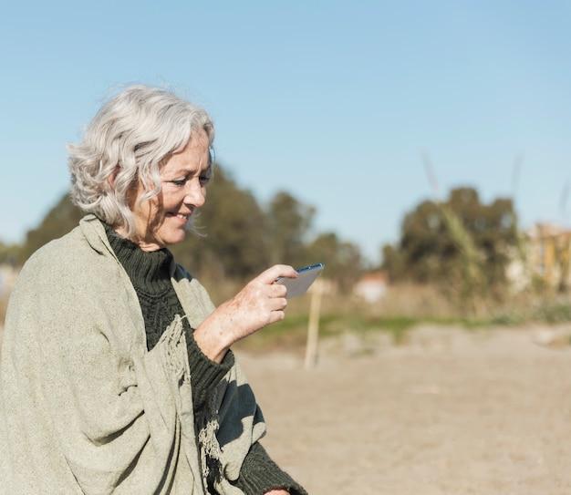 スマートフォンでミディアムショット老婦人