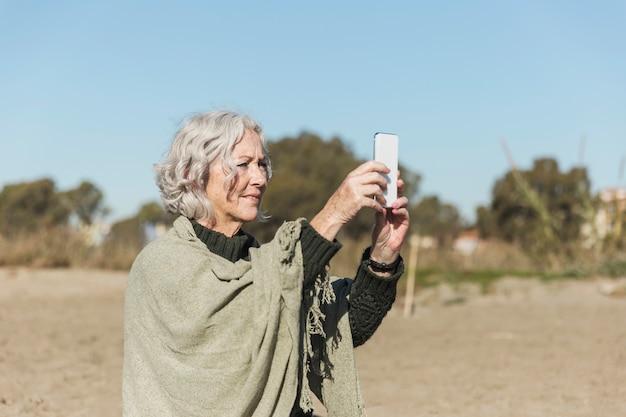 Средний снимок женщина делает фотографии на открытом воздухе