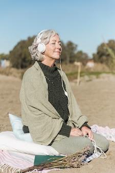 Полный выстрел женщина медитирует на открытом воздухе