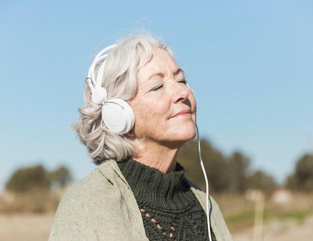 目を閉じて、ヘッドフォンでミディアムショットの女性