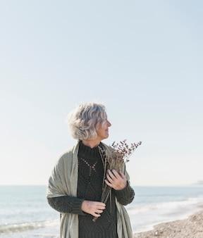 Средний выстрел женщина на пляже с цветами