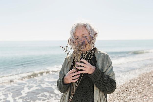 Средний снимок женщины на берегу моря с цветами