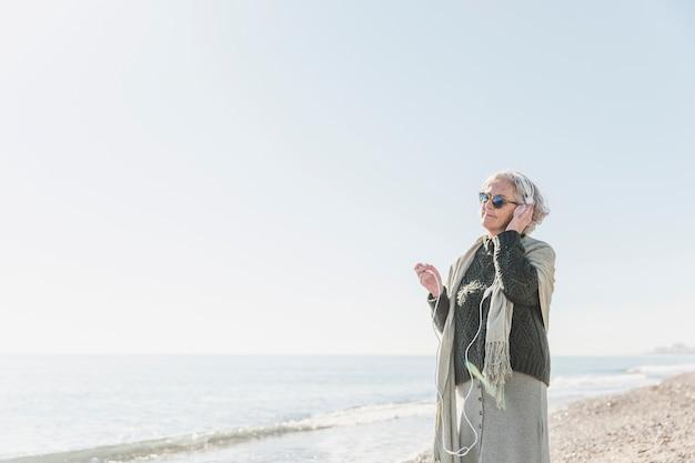屋外で音楽を聴くミディアムショット女性