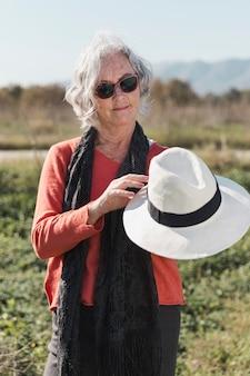 帽子を保持しているミディアムショットの女性