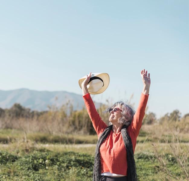 サングラスと帽子を持つミディアムショット女性
