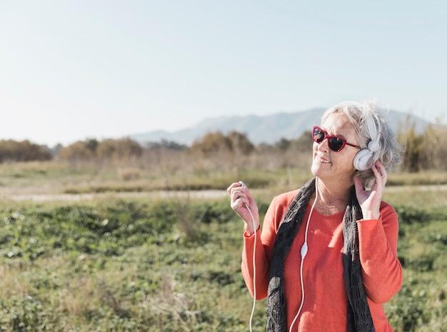 Счастливая старуха слушая к музыке