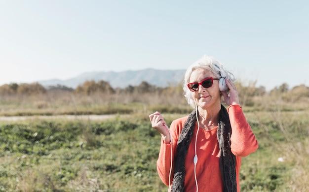 Средний выстрел женщина с наушниками на открытом воздухе