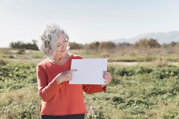 Женщина с куском бумаги на открытом воздухе