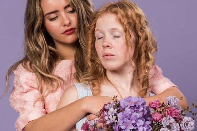 花の花束を抱き締めながらポーズをとる女性