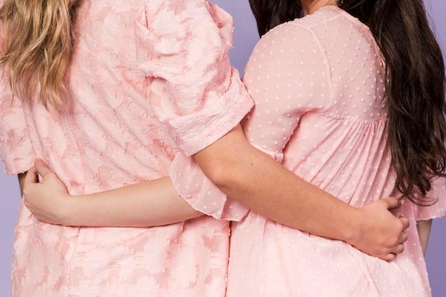Вид сзади женщин, держащих друг друга в знак сестричества