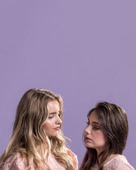 Вид спереди женщин, глядя друг на друга с копией пространства