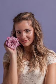 Вид спереди женщина позирует, улыбаясь и держа розу