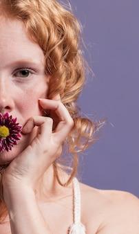 Крупным планом рыжая женщина позирует с цветком на ее рот