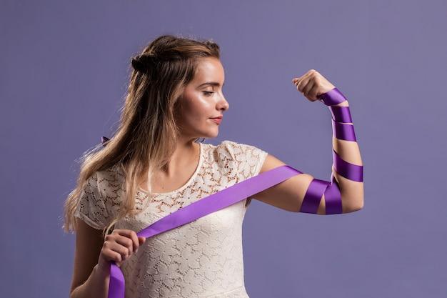Женщина сгибает руку с лентой в знак расширения прав и возможностей