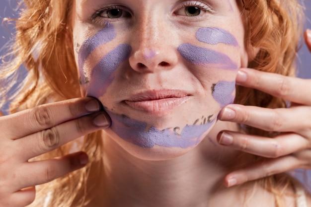 赤毛の女性が紫色の塗料で覆われて