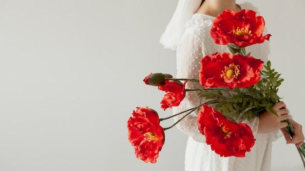 赤い花のコピースペースを保持している女性
