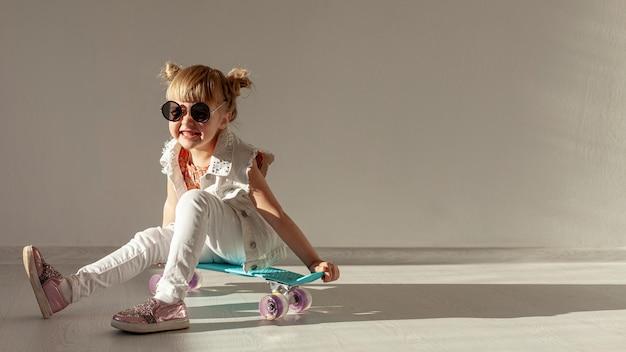 スケートボードの上に座って幸せな幼児