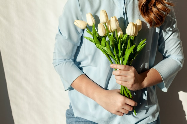 До неузнаваемости женщина держит тюльпаны