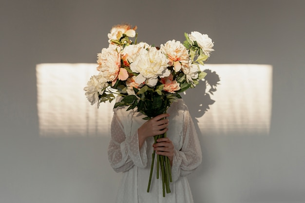 Женщина держит огромный букет цветов