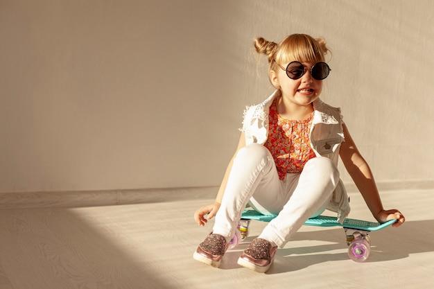 スケートボードの上に座って幸せな女の子