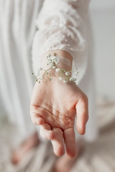 手にテープで留められた花をクローズアップ