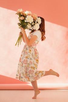 花の花束の完全なショットを保持している女性