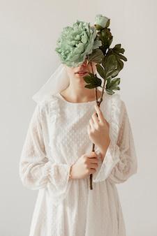 花を保持しているエレガントな女性