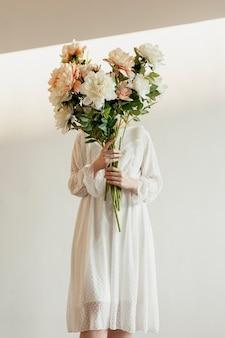 素敵な花束を保持しているエレガントなモデル