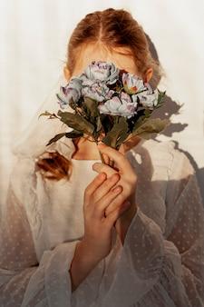 花の花束を保持しているエレガントな女性