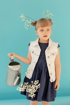 水まき缶を保持しているファッショナブルな幼児