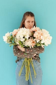 花の花束を保持している素敵な女性