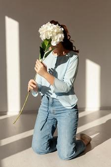 新鮮な春の花を保持している女性