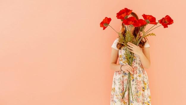 赤い花を保持している女性