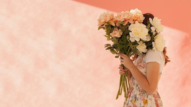 美しい花を保持している女性