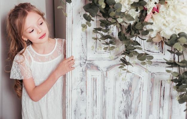 ドアの横にポーズの罪のない女の子