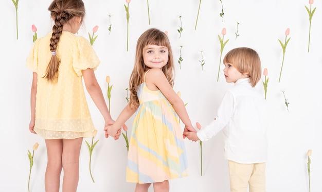 Очаровательные дети держатся за руки вид сзади