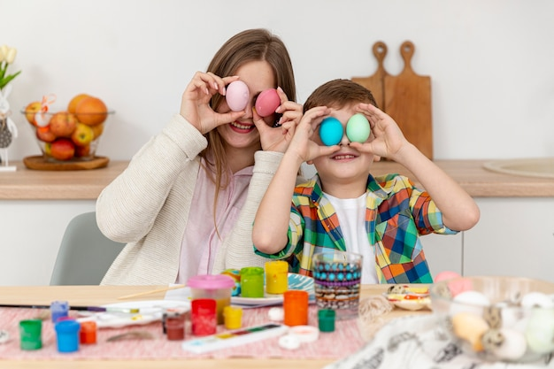 Вид спереди мама и сын с крашеными яйцами